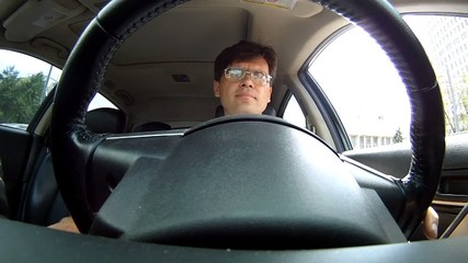 Intelligent man wearing spectacles sits in car salon