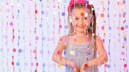 girl behind curtain from threads with multi-colored round plates moves apart and shifts it