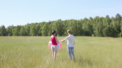 guy and girl in field also try to start kite from earth