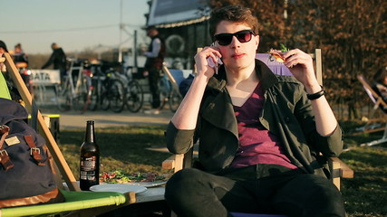 Student eating pizza and talking on cellphone in outdoor bar