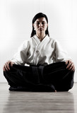 beautiful woman wearing a hakama meditating in a sports hall