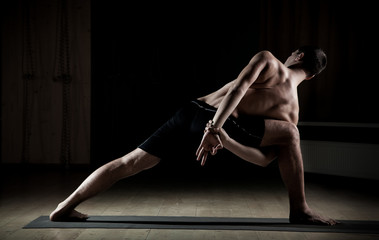 man doing yoga in a sports hall 3
