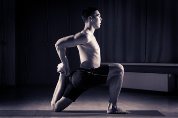 young man doing yoga in a sports hall 3