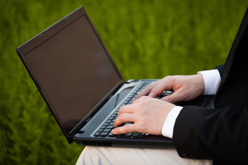 Businessman pressing modern laptop computer on colorful backgrou