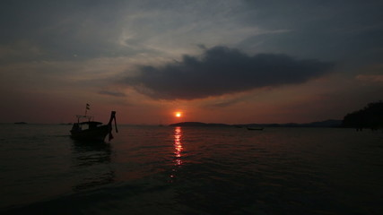 silhouette of thailand motor longtail boat rolls on waves at sun