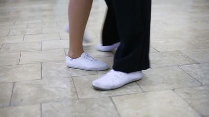 Legs of man and woman dancing boogie-woogie on marble floor