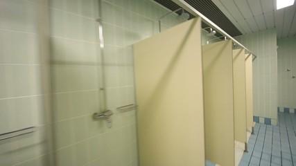 Large public shower room with several of shower enclosures