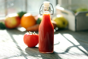 Bottle of tomato juice with fruits and vegetables on windowsill
