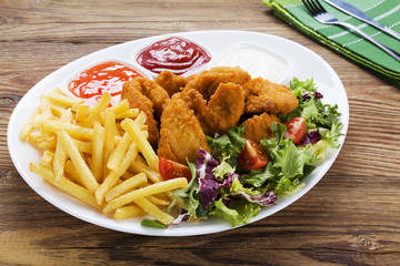 Nuggets and chips on a plate served with dip and salads