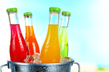 Bottles of tasty drink in metal bucket with ice