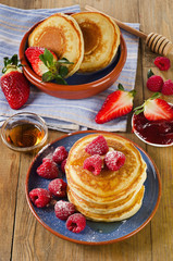 Small pancakes with berries and maple syrup.