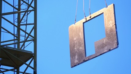 Concrete slab hangs on slings against sky while crane lifts it.