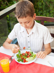 Child eating salad at a cafe