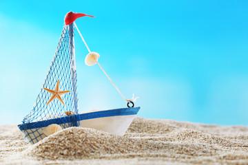 Toy model of ship on sand on blue background