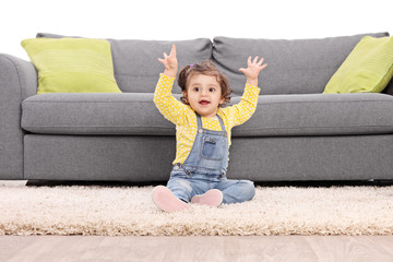 Playful baby girl gesturing happiness seated on floor