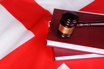 Wooden gavel and books on England flag background
