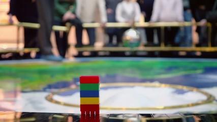 Metal sphere pendulum sways near colorful toy blocks