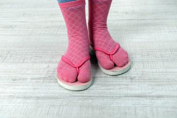 Female feet in socks with pink flip-flops, on floor background