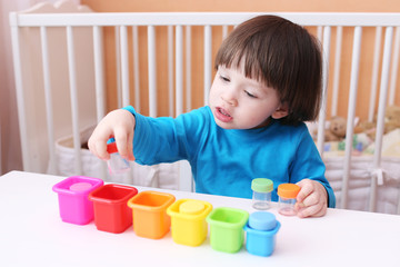 lovely 2 years boy plays with colors