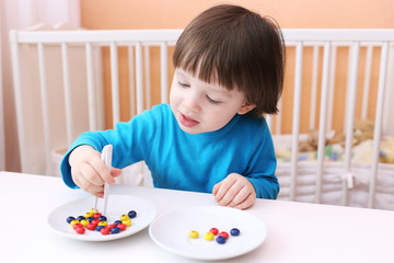 Happy little boy plays with pincers and beads. Educational playi