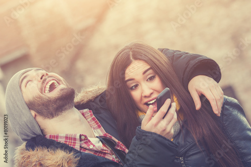 Attractive couple chilling outdoors with the cellphone.