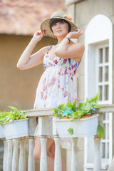 romantic brunette in hat on the balcony of his house
