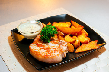 delicious pork steak with garnish on a black plate
