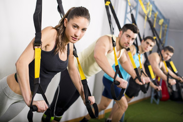 People training at gym in suspension elastic rope