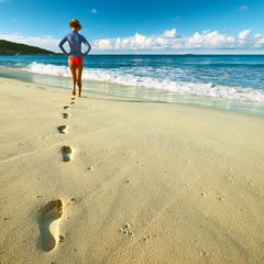 Woman at beautiful beach. Focus on footprints.