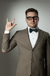 "Nerd in eyeglasses and bow tie showing ""rock on"" gesture"