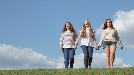 Three young girls hold hands and walk closer from behind of grass hill at sunny summer day