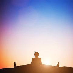 Woman in wide angle bend yoga pose meditating at sunset. Zen