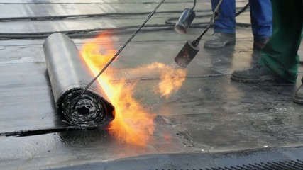 Workers use burners to roll up ruberoid for waterproofing
