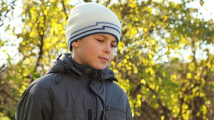 boy in a jacket and cap an autumn park by clear sunny day