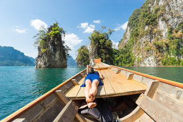 Girl on longtail boat surrounded by cliffs