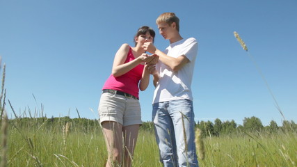 girl and guy stand in field and eat wild strawberry