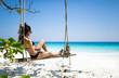 Bikini girl sitting on beach swing paradise
