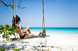 Bikini girl sitting on beach swing paradise