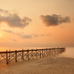 Sunset over the beautiful tropical beach with bridge