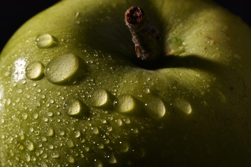 wet green macro apple with water drops on black background