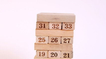 Wooden cubes with numbers are built in high tower, time lapse