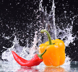 drops of water fall on the red and yellow pepper, splash