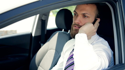 Serious business man on the phone sitting in car