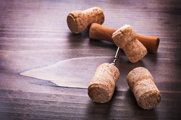 four corks and corkscrew on vintage wooden board alcohol concept