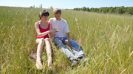 guy and girl sit together in field and eat wild strawberry