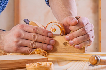 hands of carpenter in work with woodworkers plane construction c
