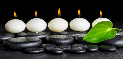 spa background of row white candles and green leaf on black zen