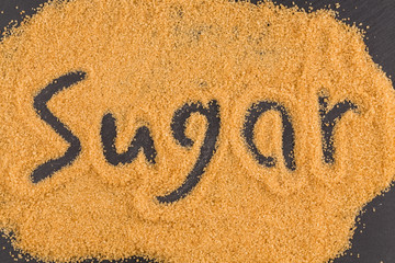 word sugar written in brown granulated sugar