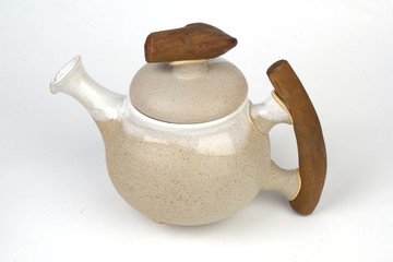 Handmade clay teapot on white