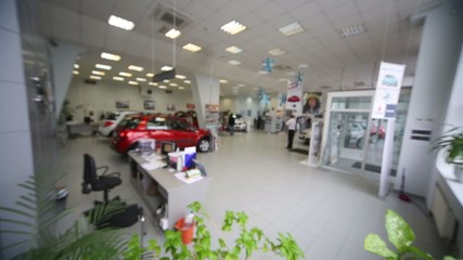 Blurred hall with green plant in office of shop selling cars